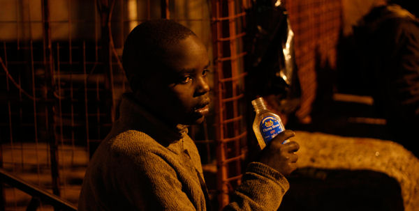 Ein Straßenkind aus Nairobi, das Kleber schnüffelt.